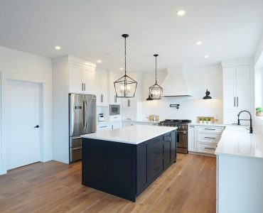 White kitchen with black cabinet island and white quartz countertops