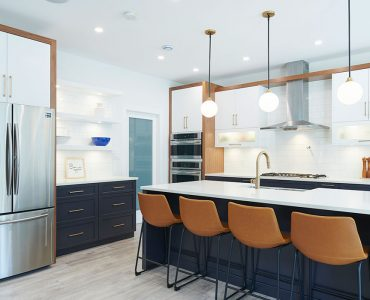 Modern kitchen with white cabinets and a navy blue island